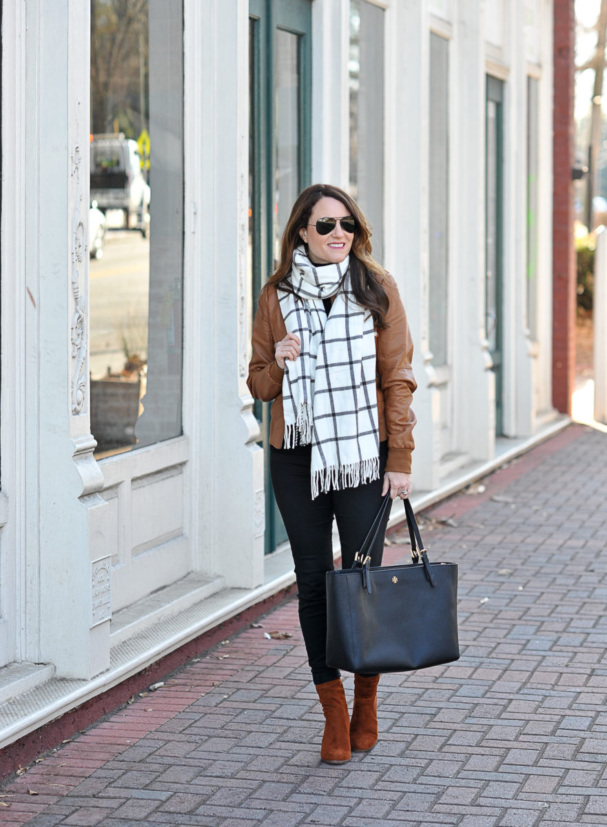How to wear a leather jacket to look chic and stay warm this winter via Peaches In A Pod blog.  Brown leather jacket, windowpane scarf, black denim and sock boots.