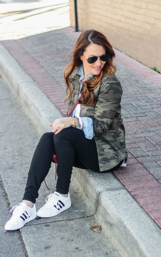 Casual spring outfit idea for women via Peaches In A Pod blog. Adidas sneakers, camouflage jacket, and Ray-Bans make for the perfect casual combination.