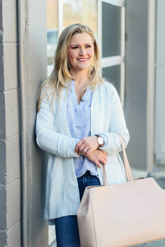 How to style a striped shirt for early spring. Paired with a gray cardigan and pink bag make a great casual outfit.
