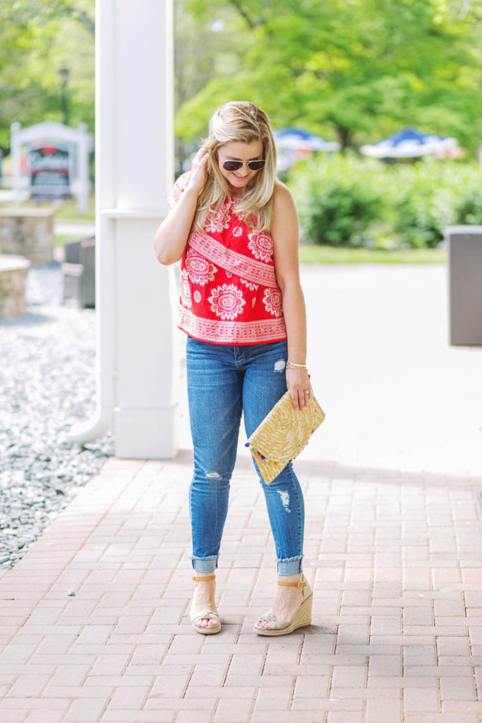 how to style a one shoulder top for Spring with nude wedges and a pom pom clutch