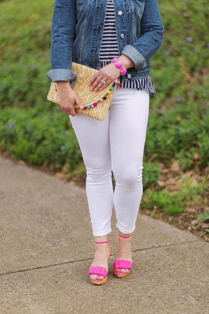 Cute white jeans outfit with a pom pom clutch to create a great casual afternoon look.