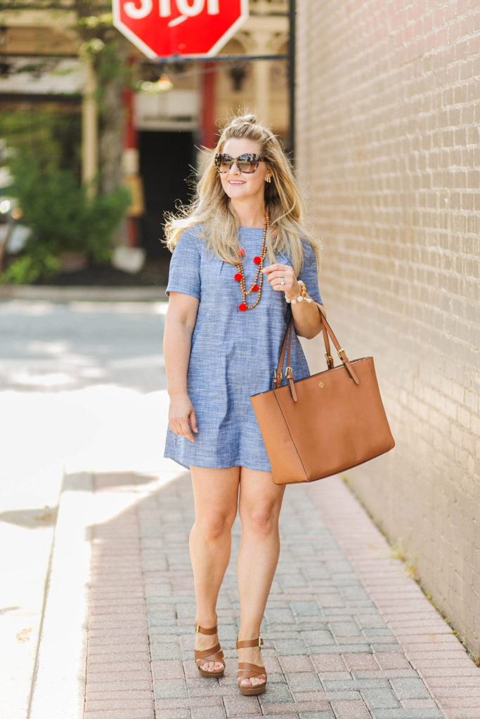 how to style a chambray dress for summer with a pom pom necklace and brown wedges.