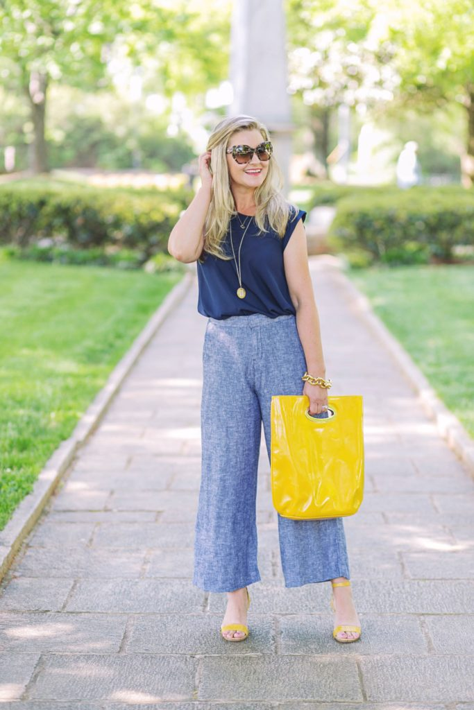 cute summer outfit with cropped wide leg pants and a yellow clutch.