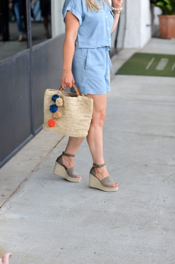 Cute pom pom straw bag with a denim romper and wedge platforms. The perfect summer look.
