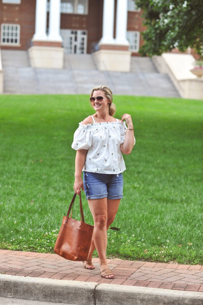summer jean shorts outfit with an off the shoulder top and tan sandals.