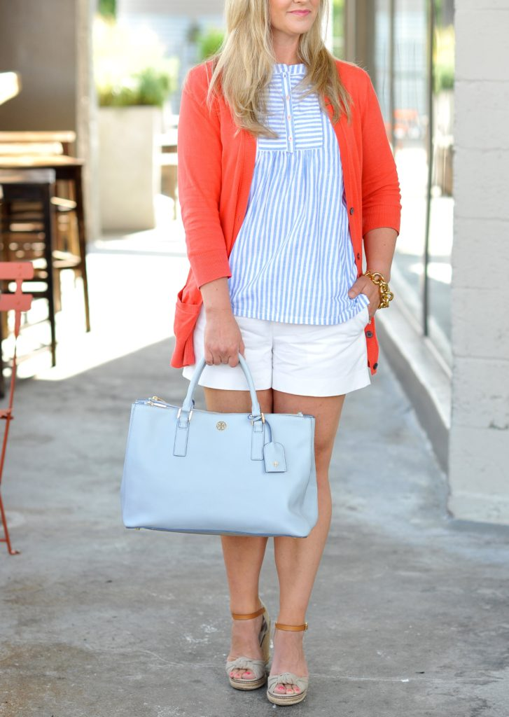 how to style white shorts in the summer with a striped top and a coral cardigan. The perfect casual style.