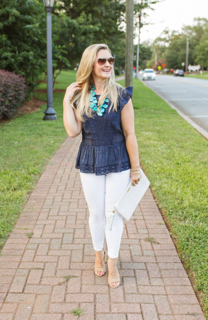 navy peplum top paired with white jeans for a great end of summer look.