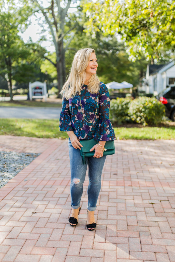 Cute fall going out outfit with a floral bell sleeve top and distressed skinny jeans