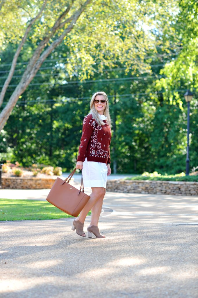 "Cute fall outfit that is the perfect casual look with a red sweater layered over a white shirt dress"" width="