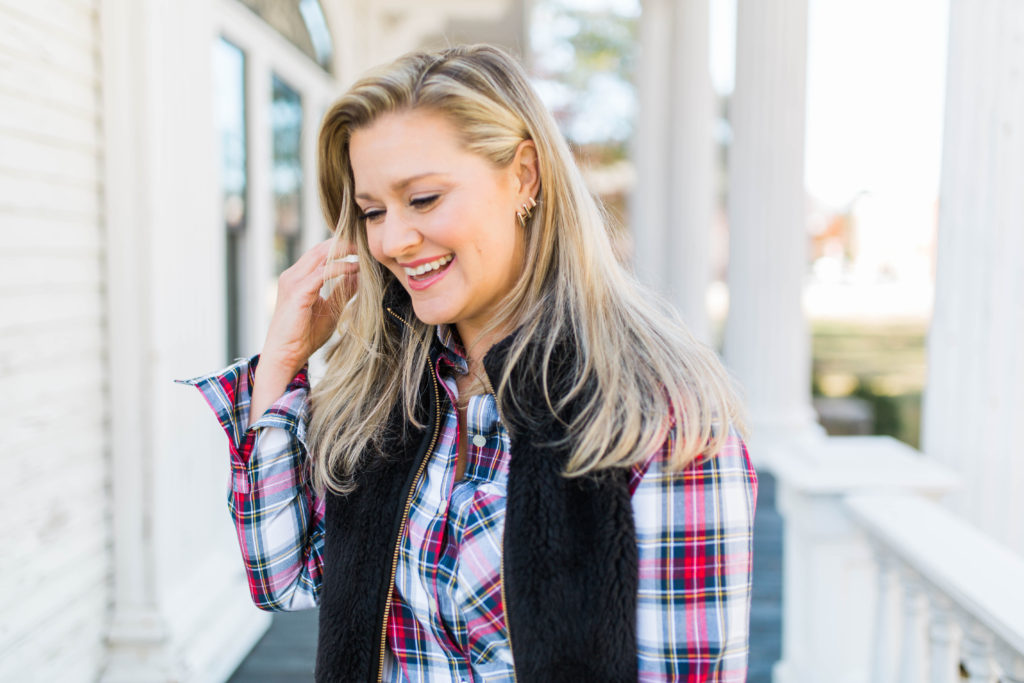 casual winter outfit that is perfect for a casual afternoon with a plaid top and a black vest.