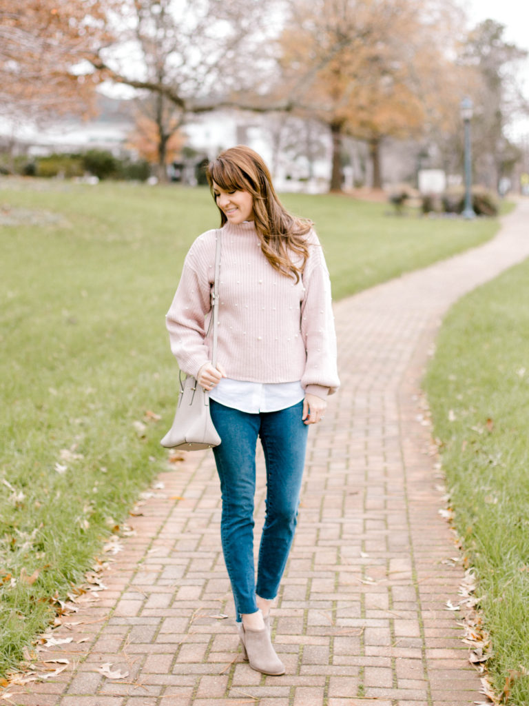 Women's winter style featuring a pink pearl embellished sweater, raw hem denim, ankle boots and gray crossbody bag.