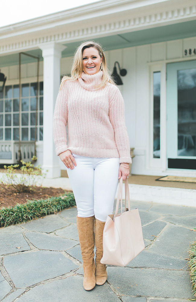 Casual white jeans outfit with a pink sweater and tall boots. Perfect for Valentine's Day.